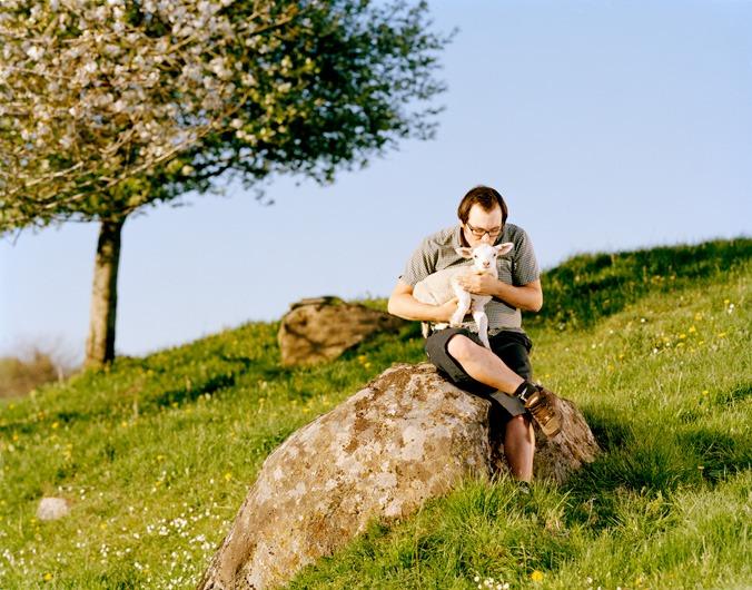 Bildet viser en mann som sitter på en stein og koser med et lam.