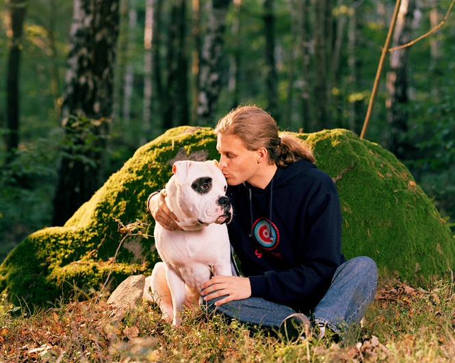 Bildet viser en mann som koser med hunden sin ute i skogen.