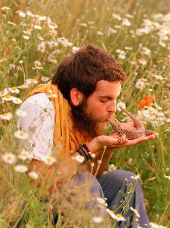 Bildet viser en mann som kysser en salamander han holder i hånden mens han sitter i en blomstereng.