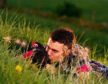 Bildet viser en mann som kysser en høne mens de ligger i gresset.