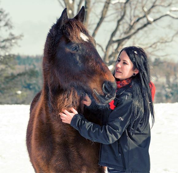En dame som koser med hesten sin ute i snøen