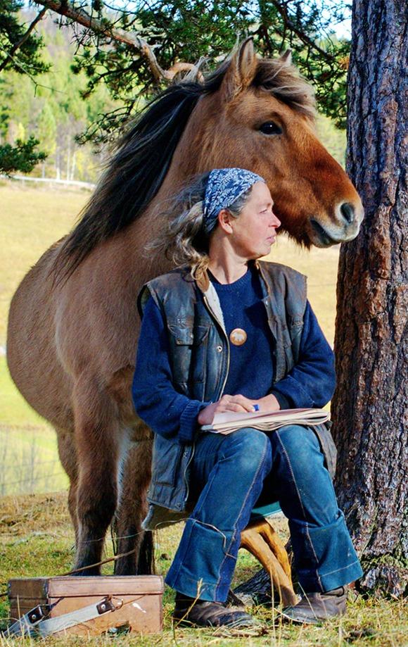 En dame som sitter under et tre sammen med en hest