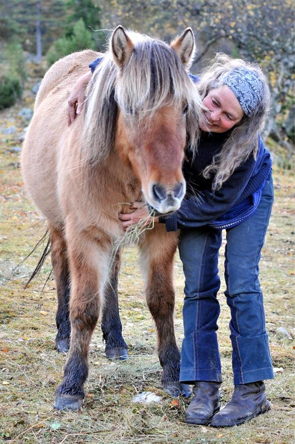 En dame som står ved siden av hesten sin og klapper den