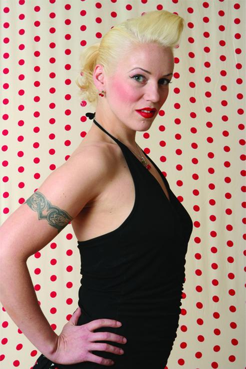 Portrett av Hilde Marstrander som står foran en prikkete vegg.