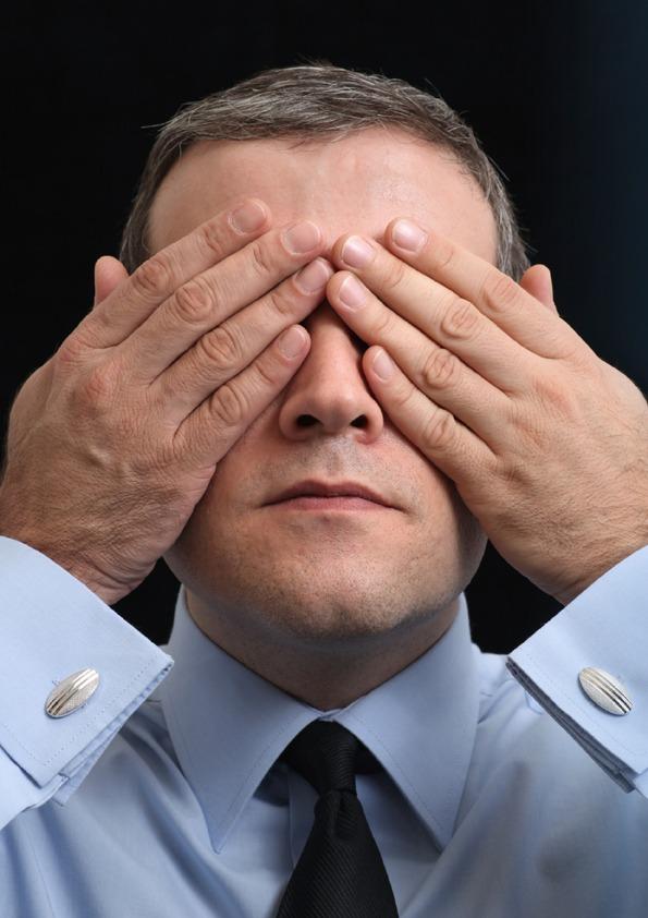 En mann som holder seg for øynene.
