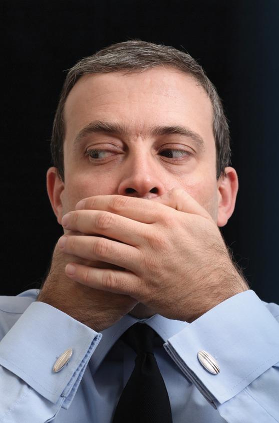 En mann som holder seg for munnen og ser til siden.