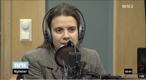 Siri Martinsen på NRK Nyheter som sitter og snakker med headset og mikrofon.