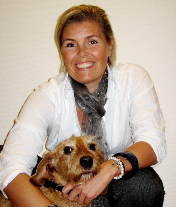 Portrett av Marie Moda som smiler mens hun holder rundt hunden sin