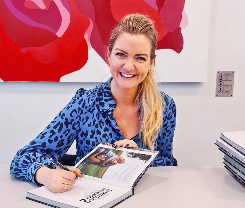 Bilde av Hanne Line Dahgren som signerer kokeboken sin smilende