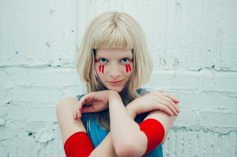 Aurora Aksnes med ansiktsmaling og hendene i kryss