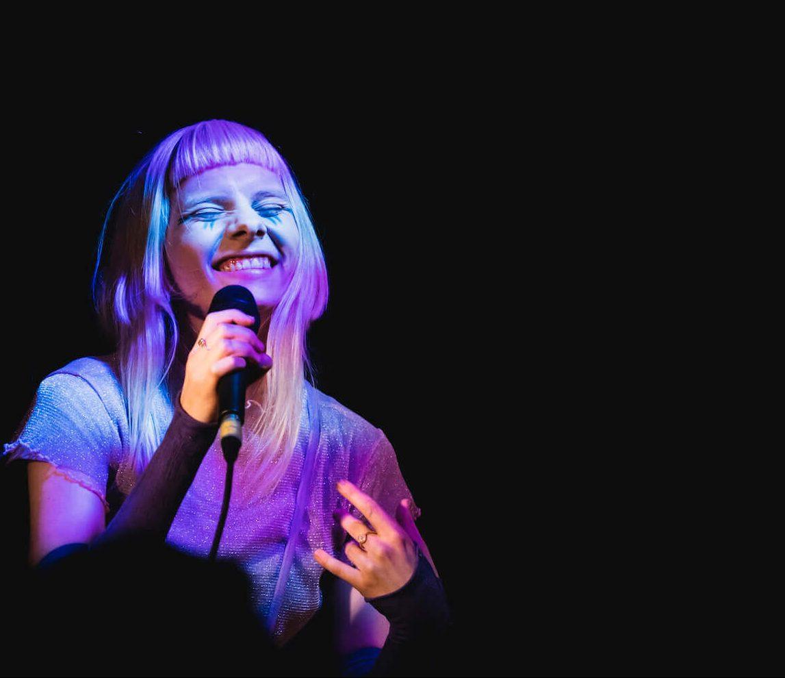Aurora Aksnes som står på scenen og smiler