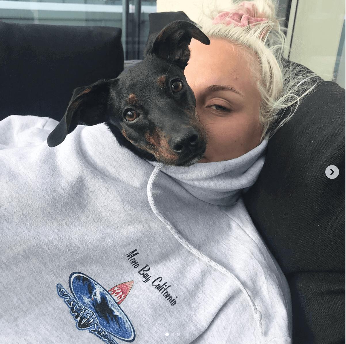Tomine Harket koser med sin lille hund Miley, som inni genseren hennes.