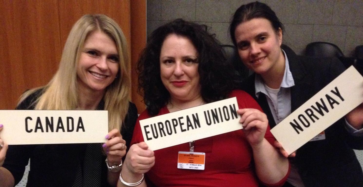 Tre smilende damer som holder skilt som representerer Canada, EU og Norge i WTO høring